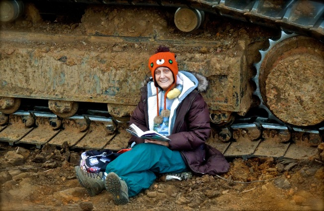 Elizabeth reading her book, locked to an excavator, shortly before being cut out.